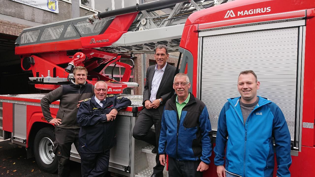 Jens Kamieth (Mitte), mit dem Leiter der Feuerwehr Freudenberg, Uwe Saßmannshausen, (2. v. r.) und Kreisbrandmeister Bernd Schneider (2. v. l.) vor dem Feuerwehrauto, mit Vertretern der Freudenberger Wehr.