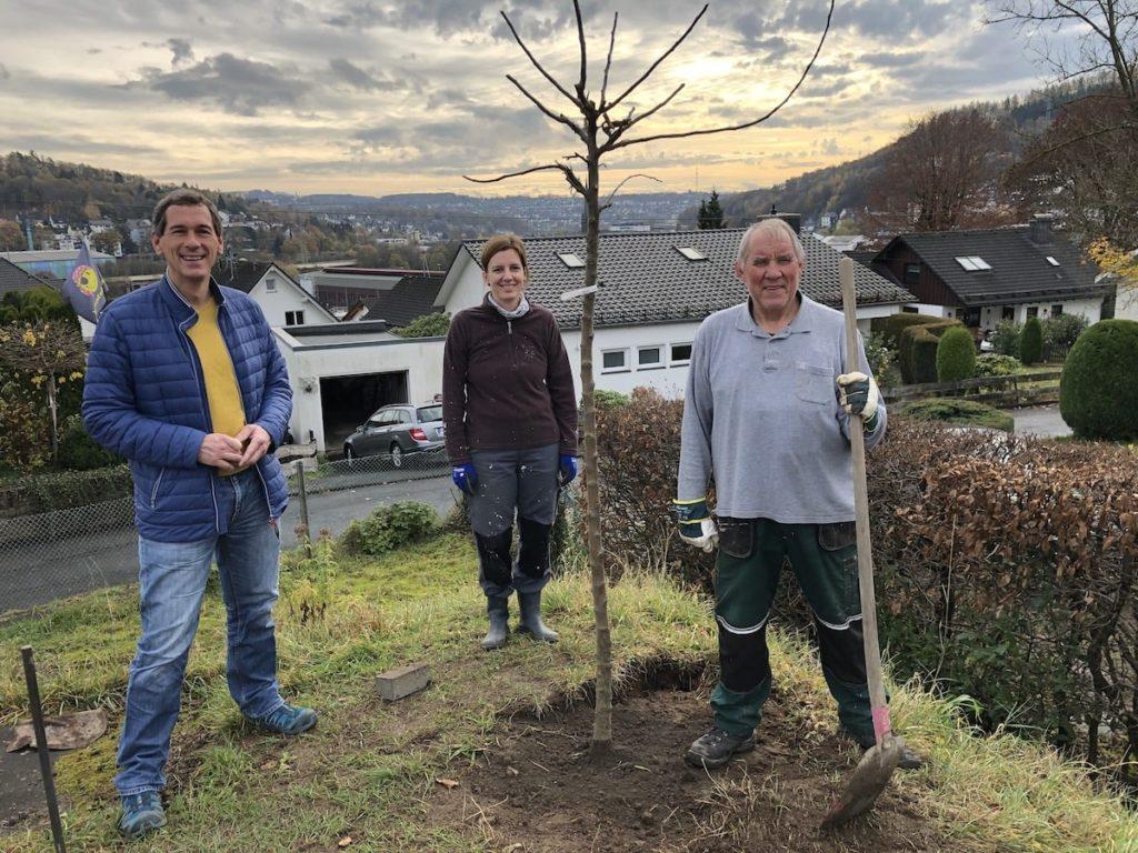 Das Foto zeigt Jens Kamieth (MdL), Verena Pittke und Achim Hölgers (Projektleiter der TG FRIESEN) beim Pflanzen eines Apfelbaumes
