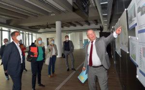 """Ulf Richter (r.), Kanzler der Universität Siegen, erläutert den Gästen um Ministerin Isabel Pfeiffer-Poensgen Details zum Projekt """"Siegen. Wissen verbindet""""."""